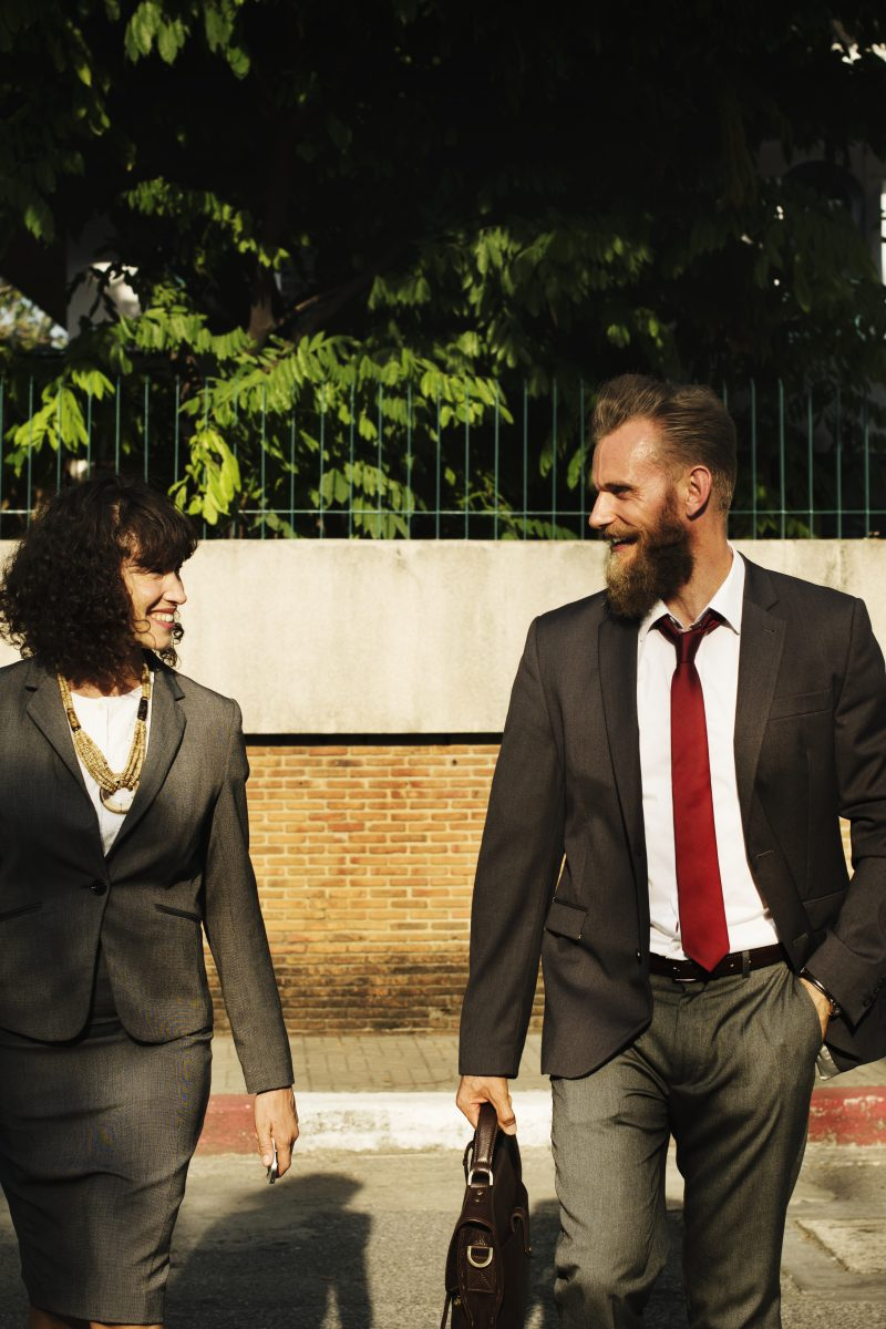 man and woman in business suits talking