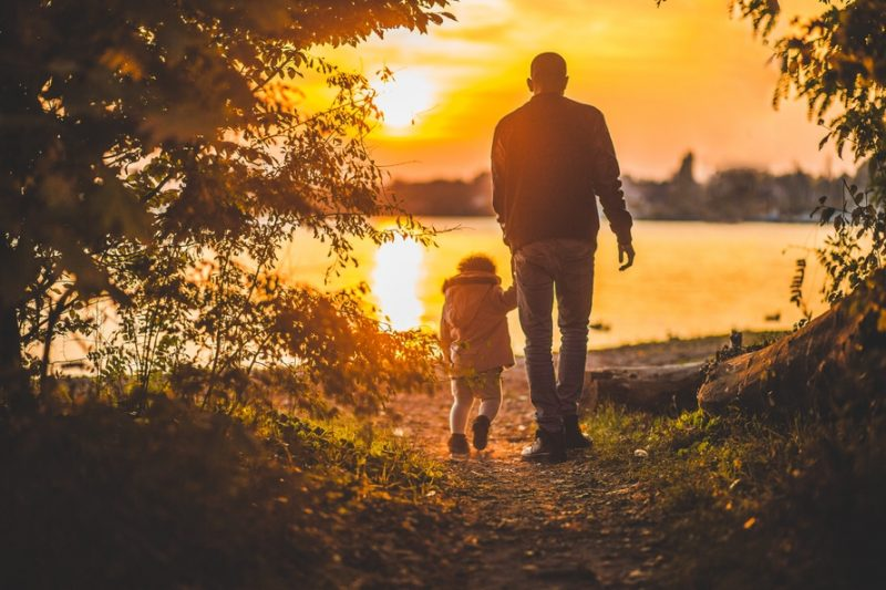 man holding toddler's hand on path