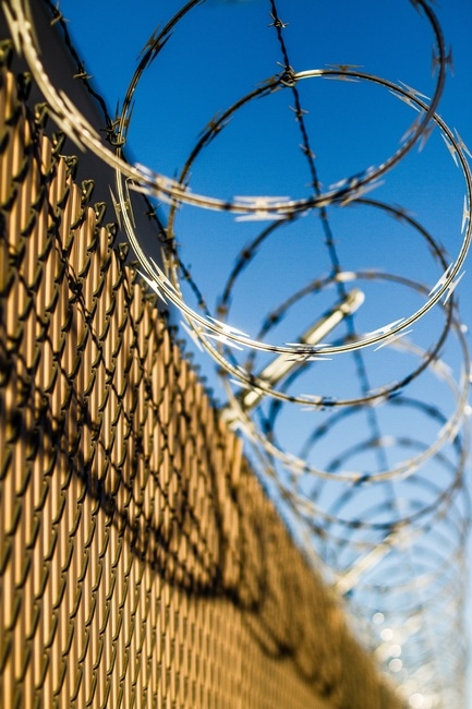 barbed wire topped fence