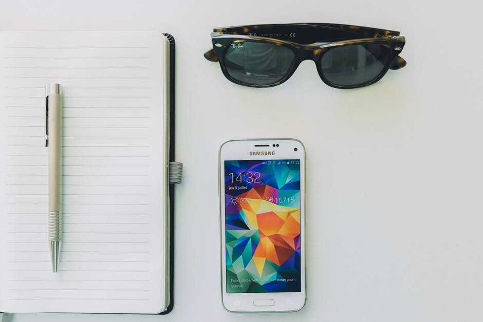 blank notebook, phone, sunglasses