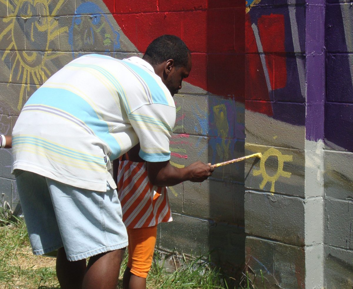 man helping child paint wall