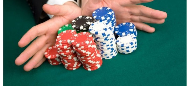 hands pushing pile of poker chips