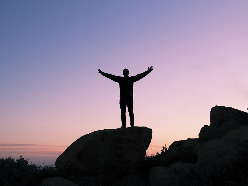 sunset silhouette of man on top of rock